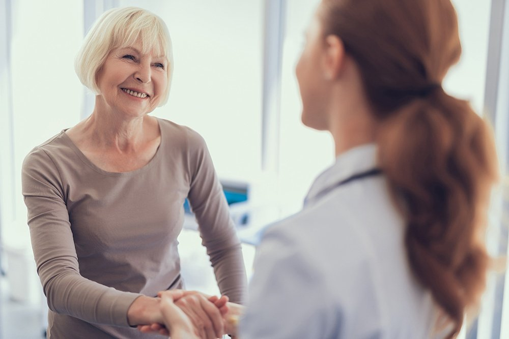 Smiling elderly woman shaking hands with physician after visit to clinic