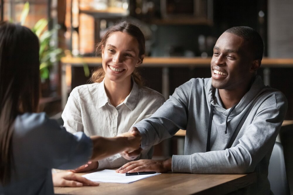 happy couple shaking hands with insurance person after signing documents