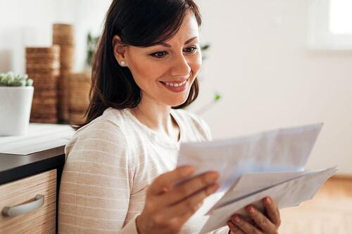 woman happily opening her mail