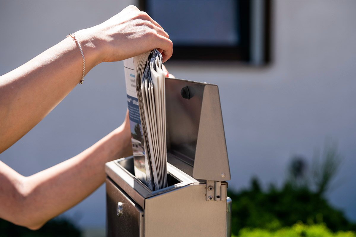 woman pulling out newspapers and mail from her mailbox