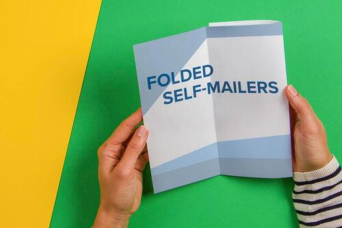 woman's hands opening folded self-mailer