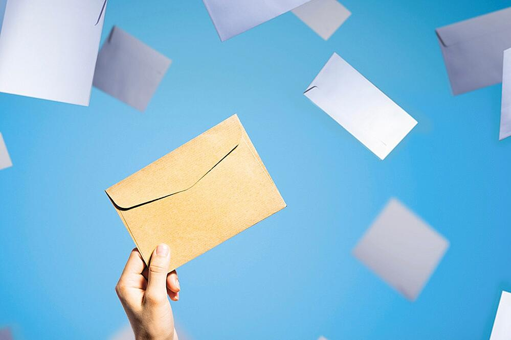 yellow envelope floating on a blue background with white envelopes floating around in the background