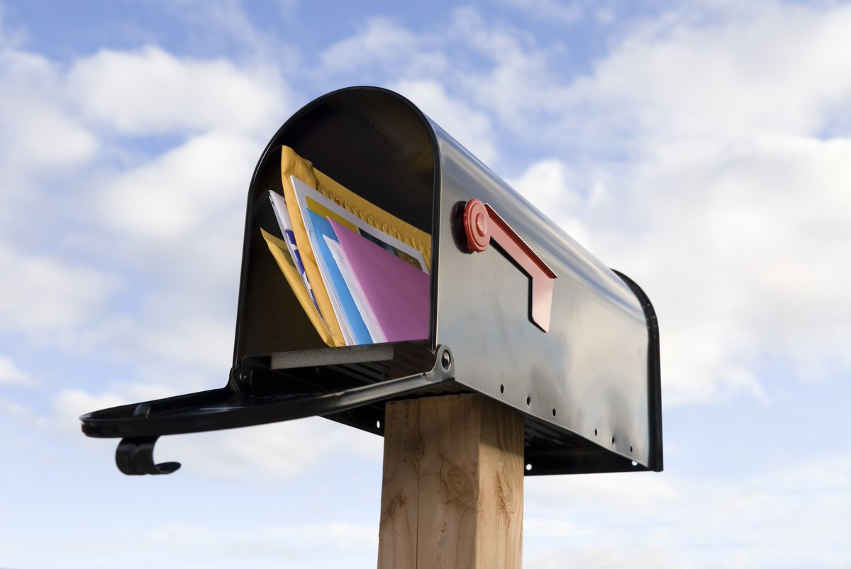 full mailbox against a cloudy sky background