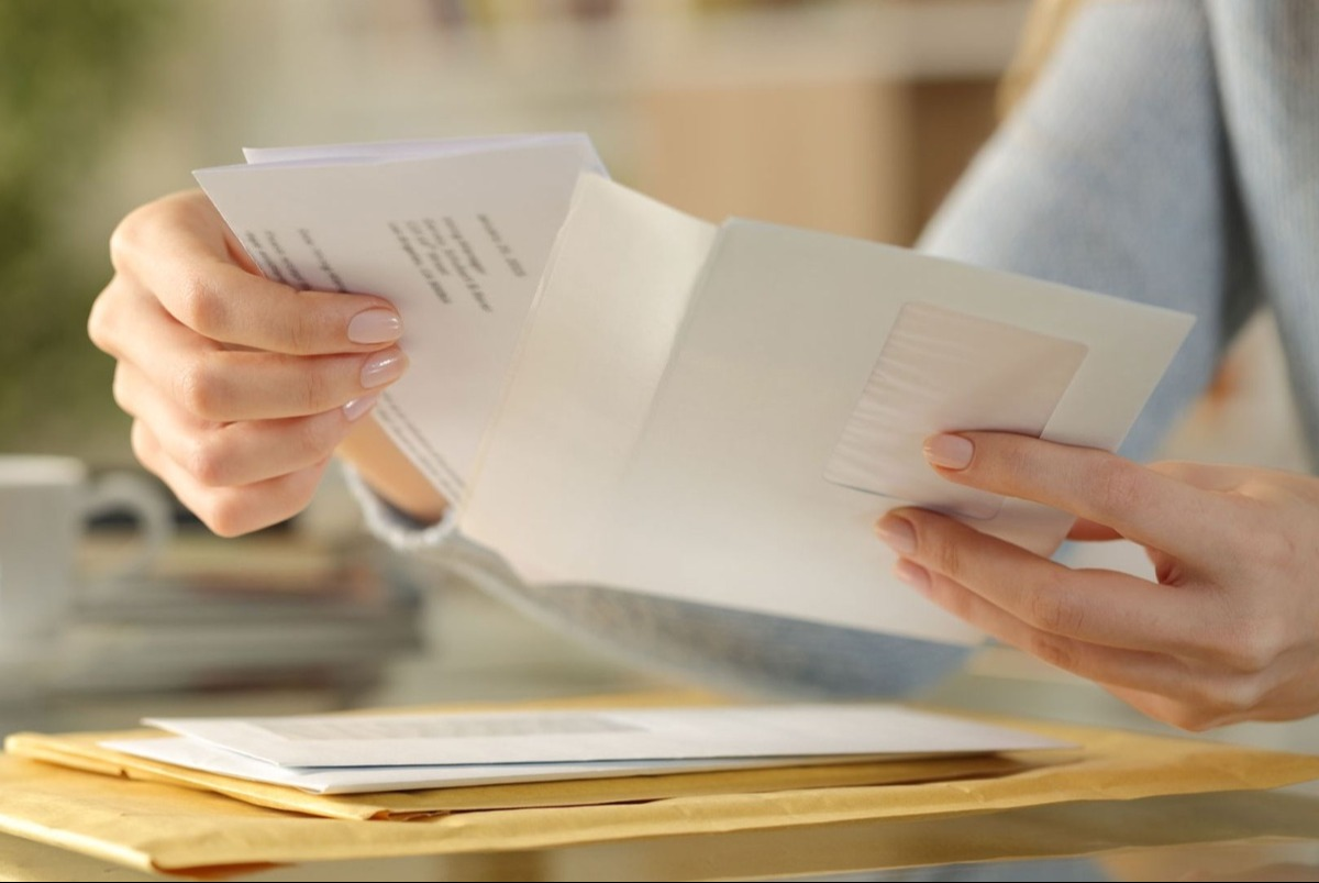 Woman's hands opening an envelope from a stack on her desk